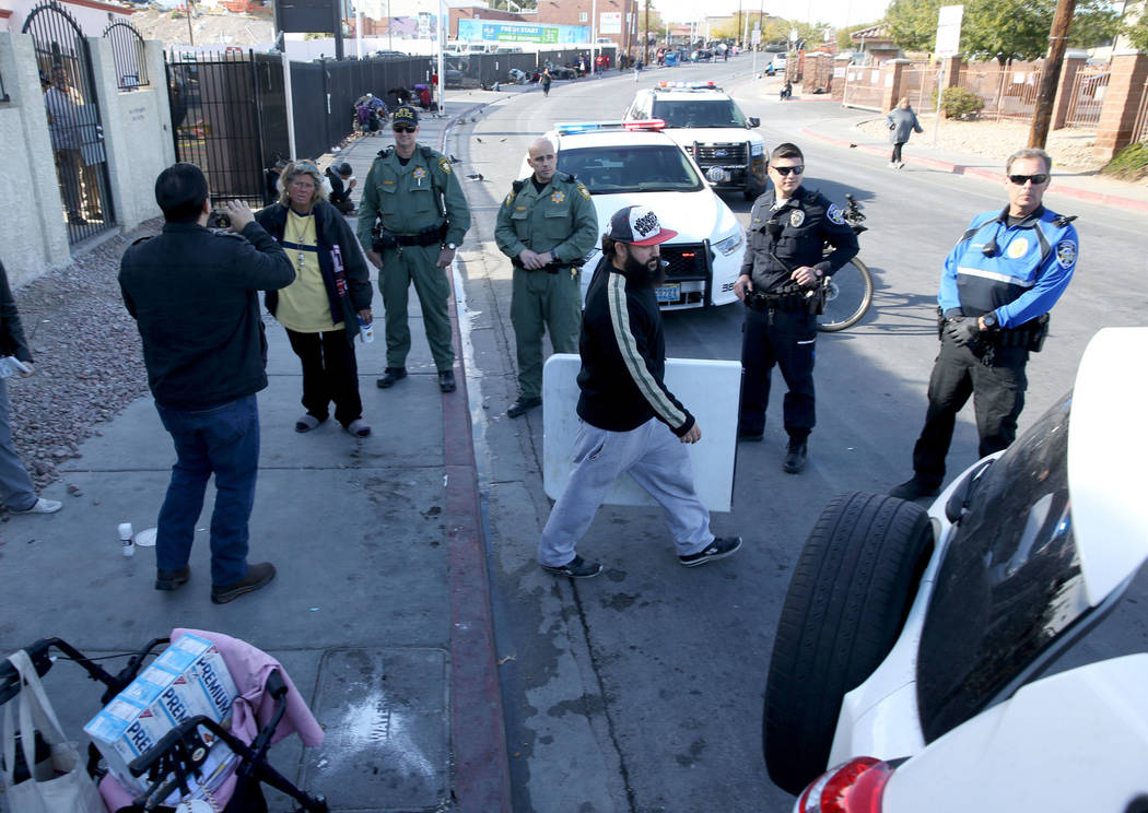 Las Vegas police watch as Joey Lankowski packs up where he was distributing food on Foremaster Lane near Las Vegas Boulevard Wednesday, Nov. 28, 2018. Lankowski was cited for parking in a red zone ...