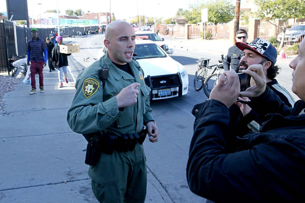 A Las Vegas police officer argues with Joey Lankowski, second from right, and Joshua Martinezm where Lankowski was distributing food on Foremaster Lane near Las Vegas Boulevard Wednesday, Nov. 28, ...