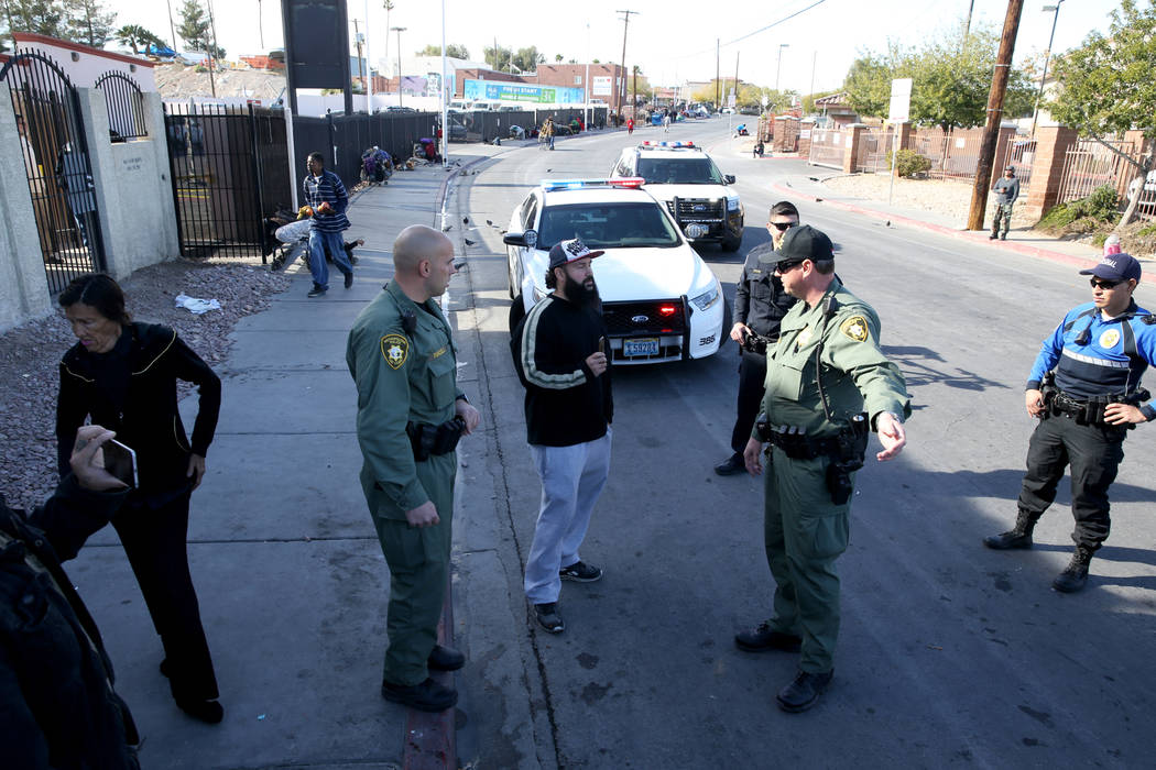 Las Vegas police argue with Joey Lankowski, center, where he was distributing food on Foremaster Lane near Las Vegas Boulevard Wednesday, Nov. 28, 2018. Lankowski was cited for parking in a red zo ...
