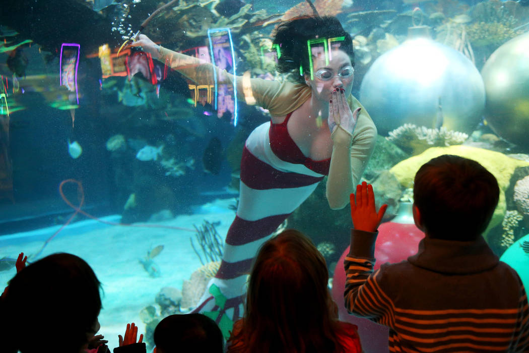 The Christmas mermaid blows a kiss to Matvay Sokolov, 6, at Silverton hotel and casino in Las Vegas, Sunday, Dec. 2, 2018. She and Santa are in the aquarium every Saturday and Sunday in December f ...