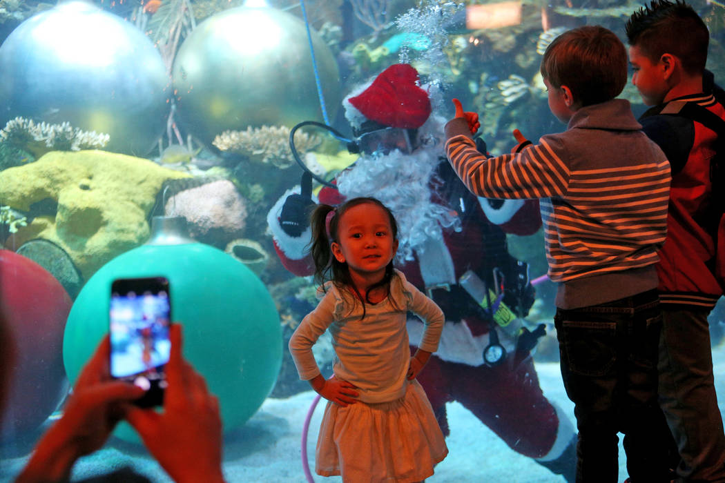Alyssa Kim, 2, has her photo taken with Underwater Santa greets the crowd at Silverton hotel and casino in Las Vegas, Sunday, Dec. 2, 2018. He and the Christmas mermaid are in the aquarium every S ...