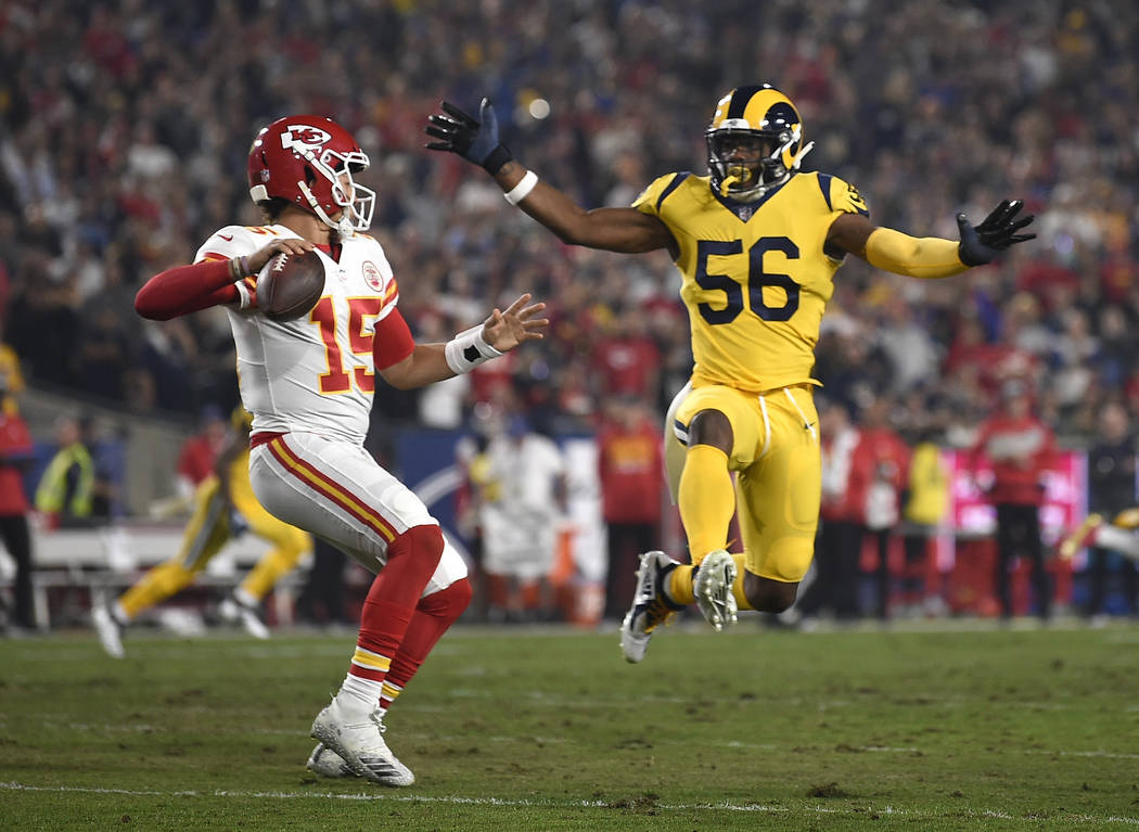 Kansas City Chiefs quarterback Patrick Mahomes, left, passes under pressure from Los Angeles Rams defensive end Dante Fowler (56) during the first half of an NFL football game Monday, Nov. 19, 201 ...