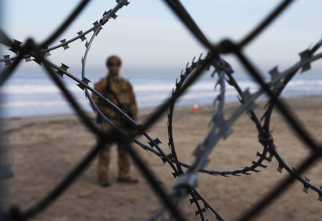 A U.S. Border Patrol agent stands on the U.S. side of the border, seen through the concertina wire from the Mexican side where the border meets the Pacific Ocean, Friday, Nov. 16, 2018. (AP Photo/ ...