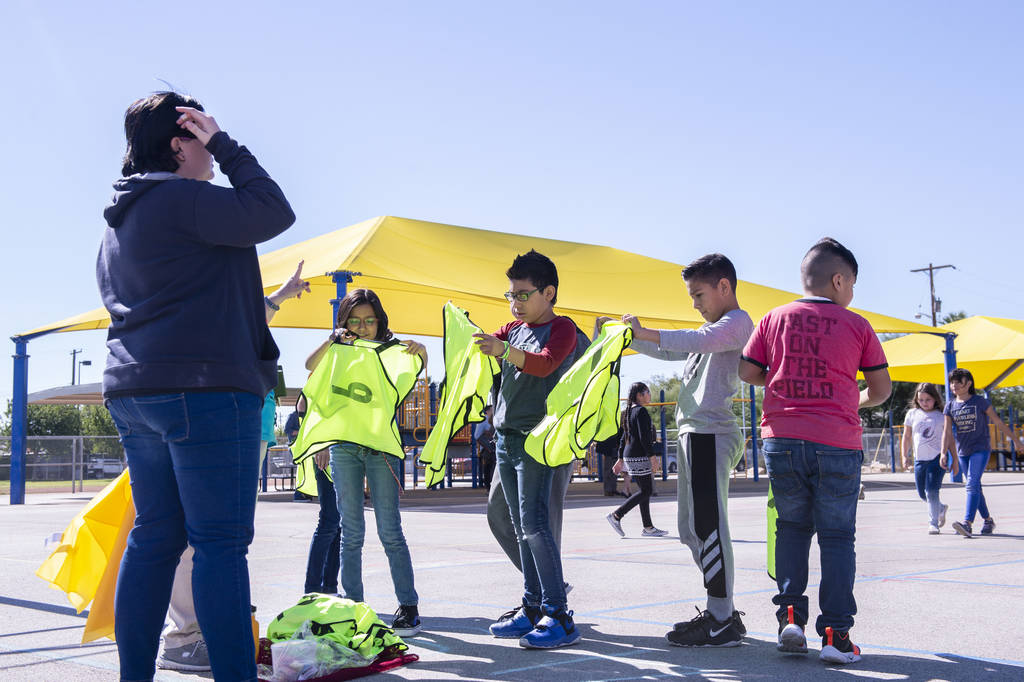 "As a part of the ""Recess Reboot"" program a group of children grab yellow vests who are in charge of leading recess activities at Walter Bracken Elementary School in Las Vegas, Wednesday, ..."