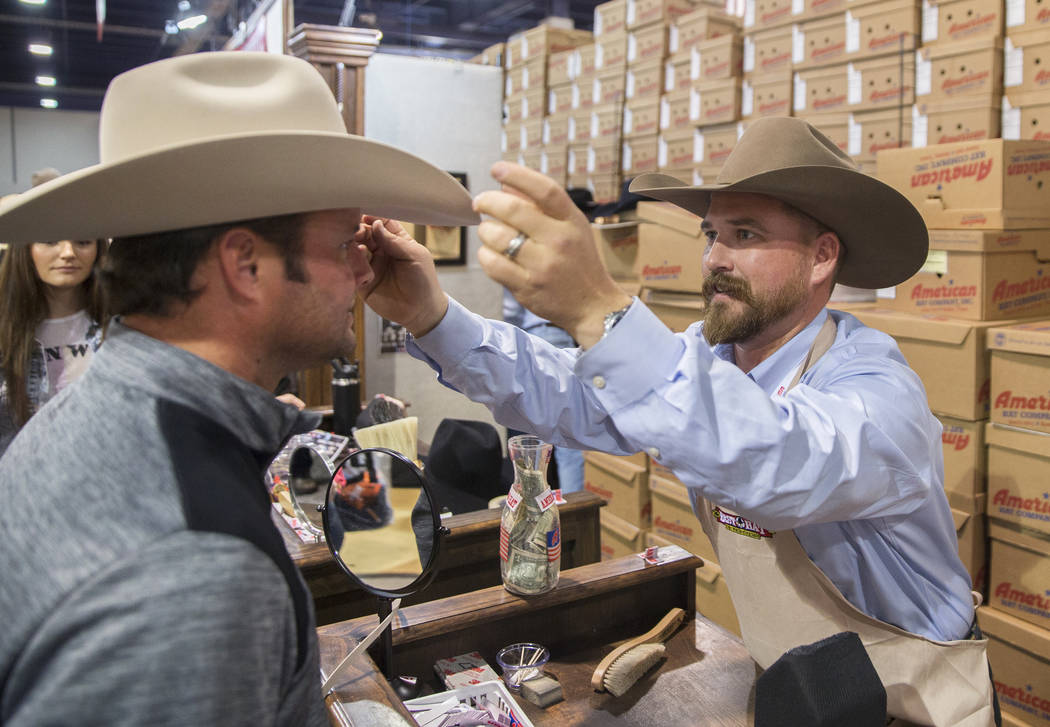 Tye Chesser, right, a sales rep at American Hat Company, helps a customer during Cowboy Christmas at the Las Vegas Convention Center on Thursday, Dec. 6, 2018, in Las Vegas. Benjamin Hager Las Veg ...