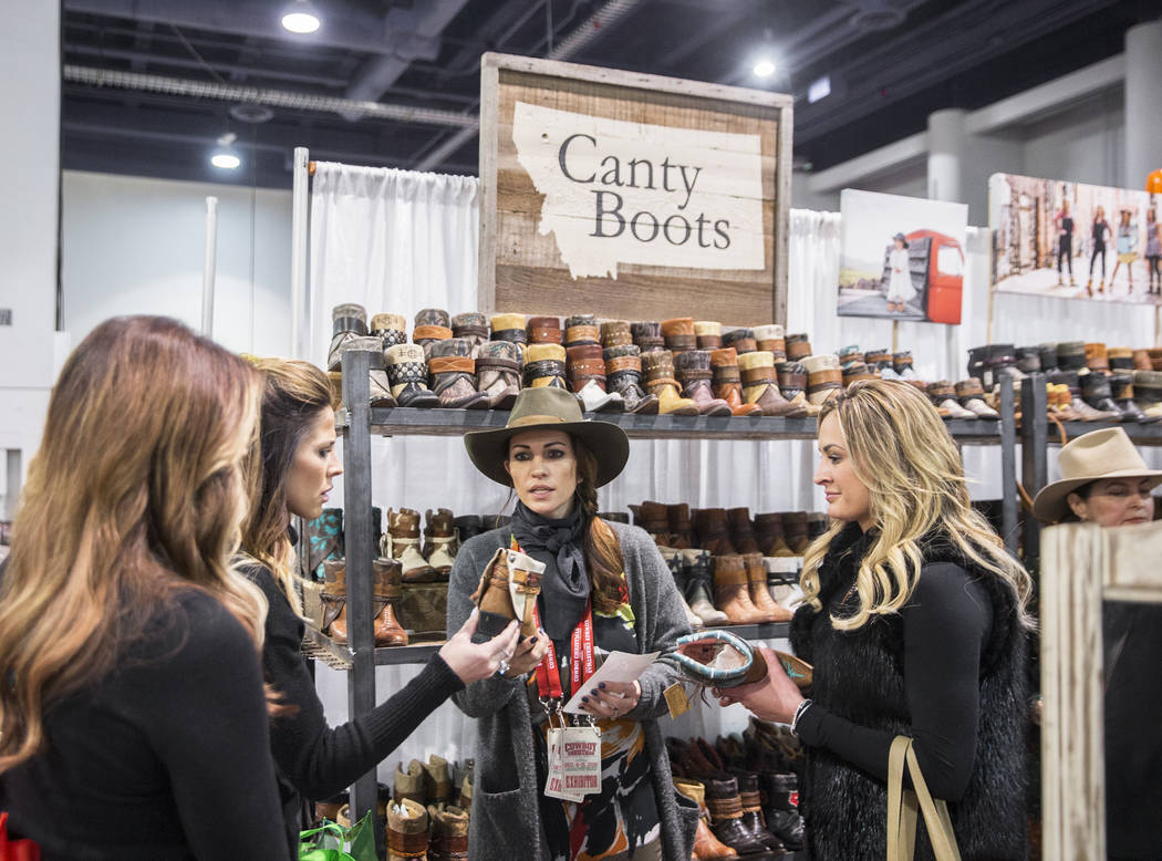 Nikki Edmundson, middle, helps customers at Montana-based Canty Boots during Cowboy Christmas at the Las Vegas Convention Center on Thursday, Dec. 6, 2018, in Las Vegas. Benjamin Hager Las Vegas R ...