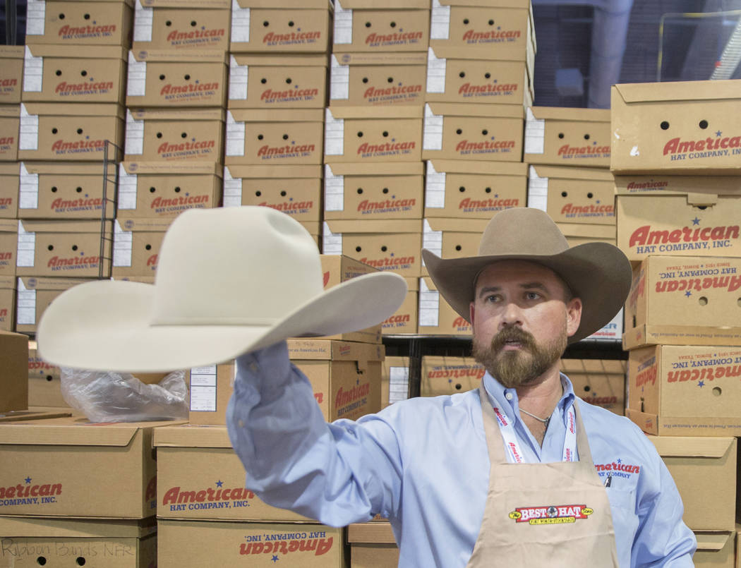 Tye Chesser, a sales rep at American Hat Company, helps a customer during Cowboy Christmas at the Las Vegas Convention Center on Thursday, Dec. 6, 2018, in Las Vegas. Benjamin Hager Las Vegas Revi ...
