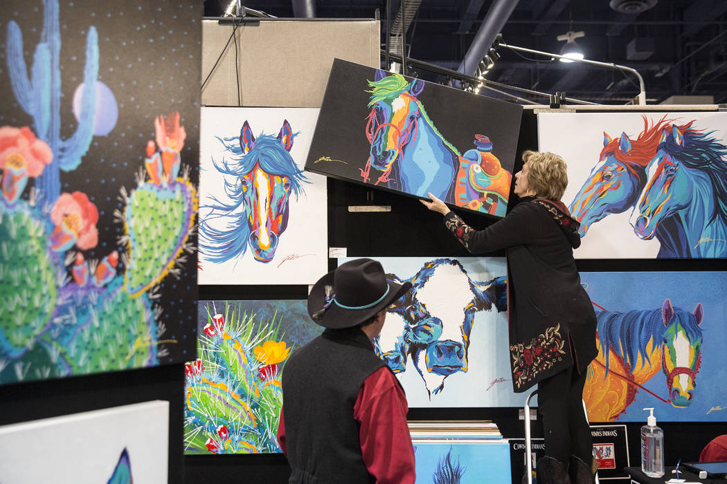 Artist Lyndon Gaither, left, from Dallas, Texas, and wife Barbara hang a painting at Contemporary Western Art at Cowboy Christmas at the Las Vegas Convention Center on Thursday, Dec. 6, 2018, in L ...