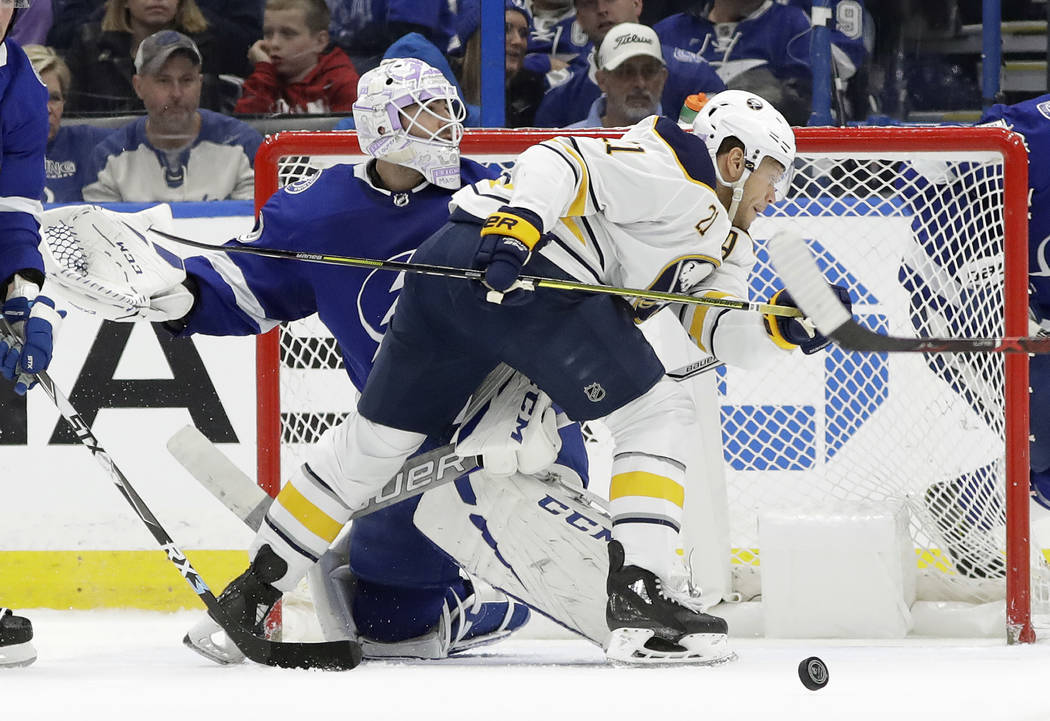 Buffalo Sabres right wing Kyle Okposo (21) runs into Tampa Bay Lightning goaltender Louis Domingue (70) after the puck hit the post during the second period of an NHL hockey game Thursday, Nov. 29 ...