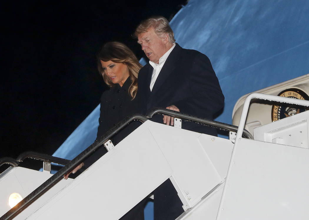 U.S. President Donald Trump and first lady Melania Trump alight from Air Force One, Sunday, Dec. 2, 2018, at Andrews Air Force Base, Md. Trump is returning from the G20 Summit in Argentina. (AP Ph ...