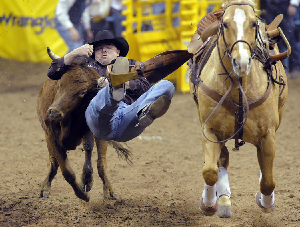 Steer wrestler Matt Reeves of Cross Plains, Texas wrestles a steer to a three way tie sixth place time of 4.30 seconds during the steer wrestling competition of the seventh go-round of the 54th Wr ...