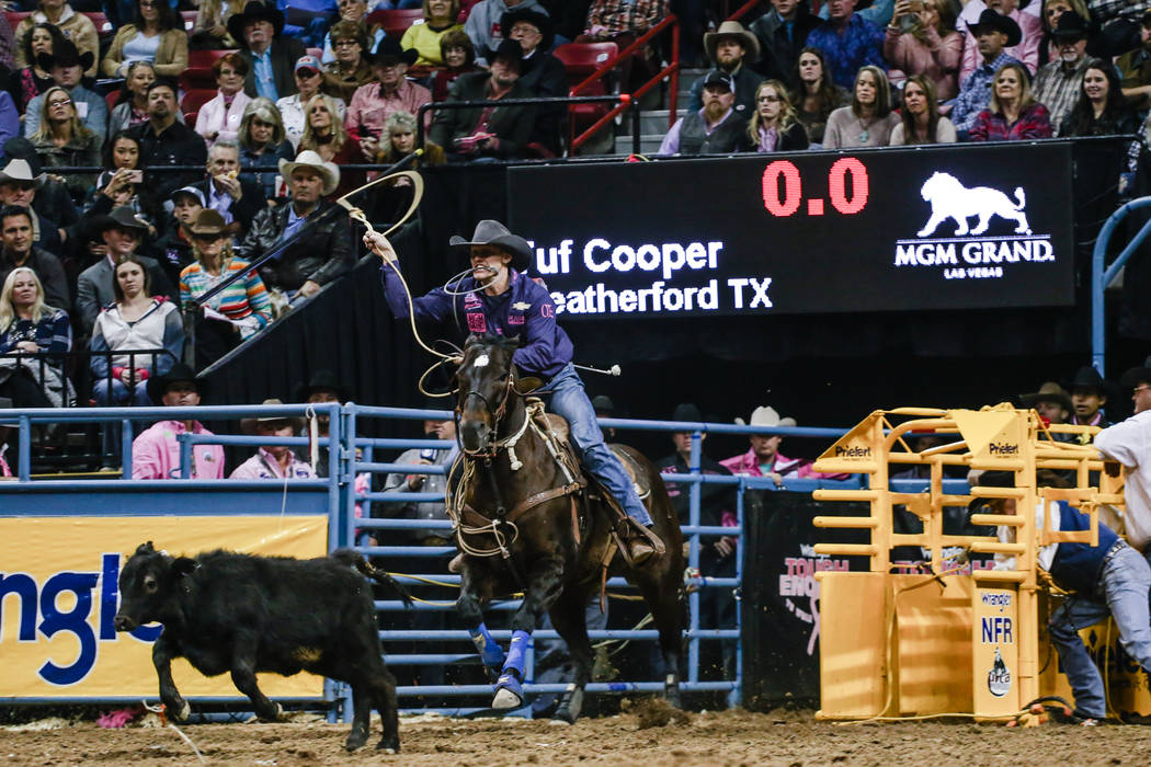 Tuf Cooper of Weatherford, Texas chases down a steer in the tie-down roping event during the fifth night of the 59th Wrangler National Finals Rodeo at the Thomas & Mack Center in Las Vegas, Mo ...