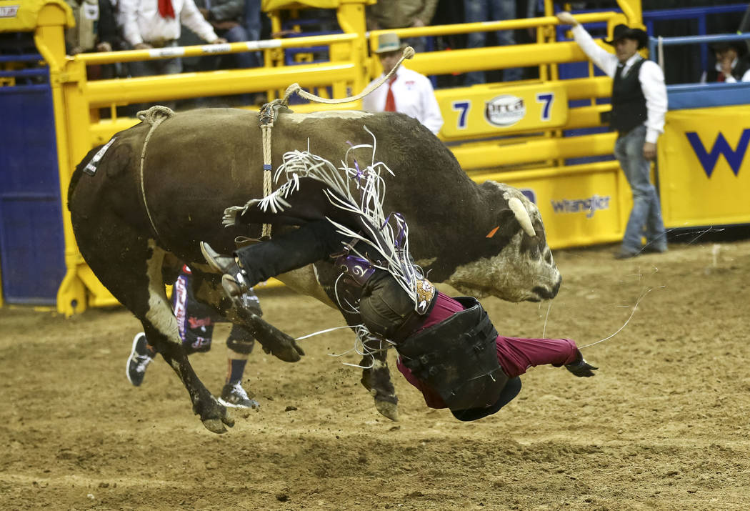 Tim Bingham of Honeyville, Utah is bucked from Red Bandana in the bull riding competition in the tenth go-round of the National Finals Rodeo, Saturday, Dec. 16, 2017, at the Thomas & Mack Cent ...