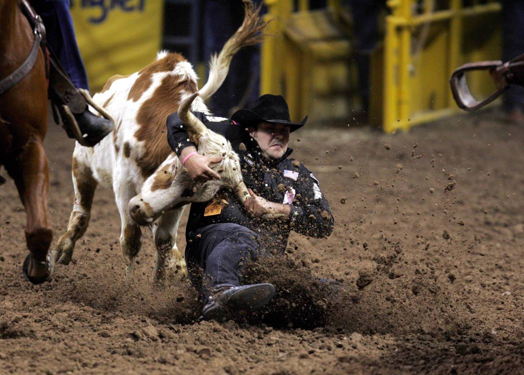 Luke Branquinho of Los Alamos, Calif., wrestles a steer in a time of 3.3 seconds to win the fifth go-around of the National Finals Rodeo at the Thomas & Mack Center Tuesday, Dec. 7, 2004. (K.M. Ca ...