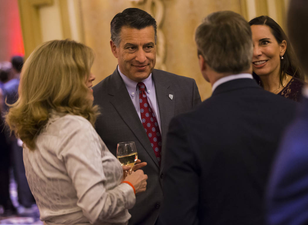 Gov. Brian Sandoval speaks alongside his wife Lauralyn McCarthy while mingling with guests during the UNLV Law Gala at the Bellagio in Las Vegas on Saturday, Dec. 1, 2018. Chase Stevens Las Vegas ...