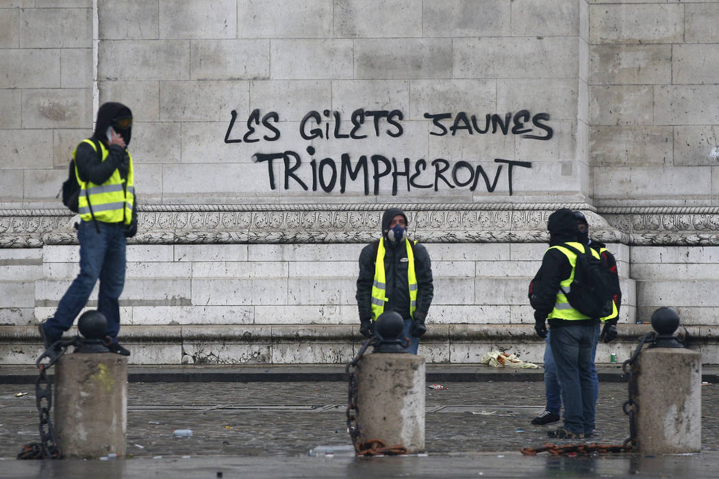 """Demonstrators stand by the words """"yellow jackets will triumph"""" written in black letters at the base of the Arc de Triomphe during a demonstration Saturday, Dec.1, 2018 in Paris. Paris po ..."""