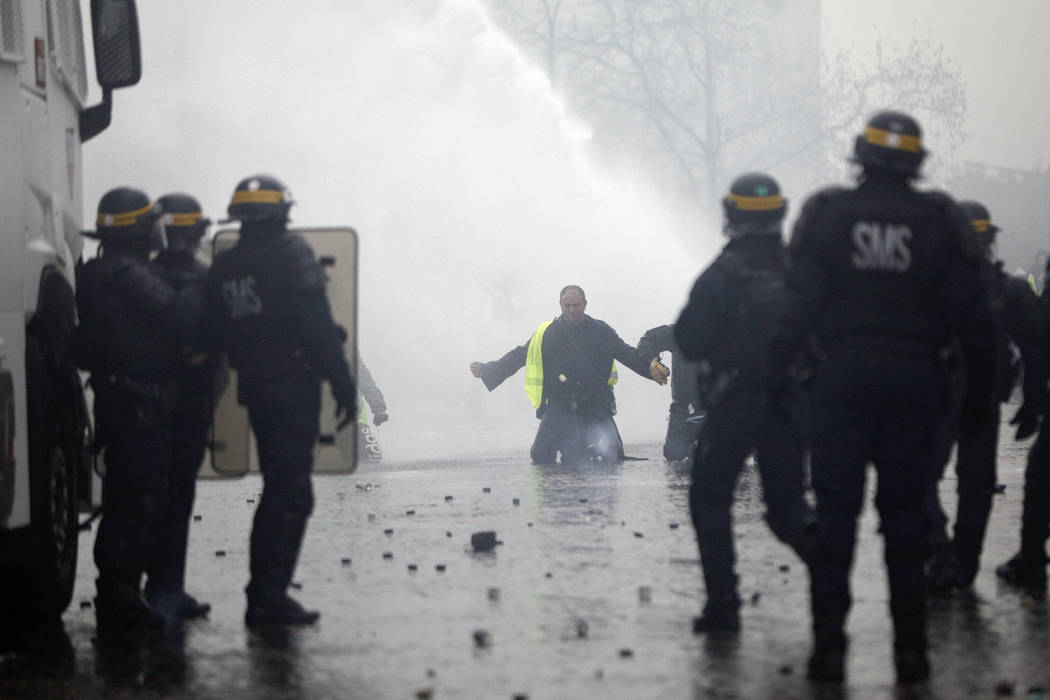 A demonstrators wearing a yellow jacket faces water cannons near the Champs-Elysees avenue during a demonstration Saturday, Dec.1, 2018 in Paris. French authorities have deployed thousands of poli ...