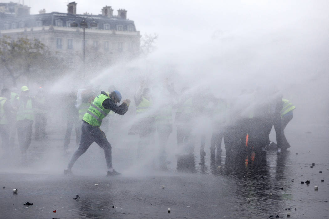 Demonstrators wearing yellow jackets face water cannons near the Champs-Elysees avenue during a demonstration Saturday, Dec.1, 2018 in Paris. French authorities have deployed thousands of police o ...