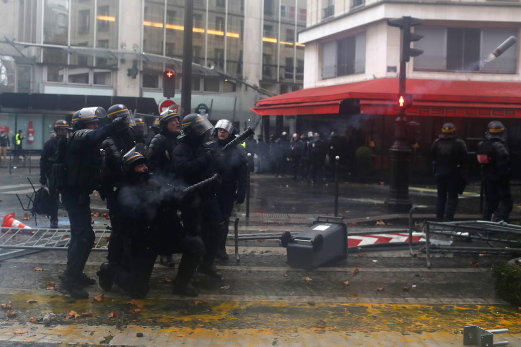Riot police officers fire tear gas canisters to demonstrators during a demonstration Saturday, Dec.1, 2018 in Paris. French authorities have deployed thousands of police on Paris' Champs-Elysees a ...