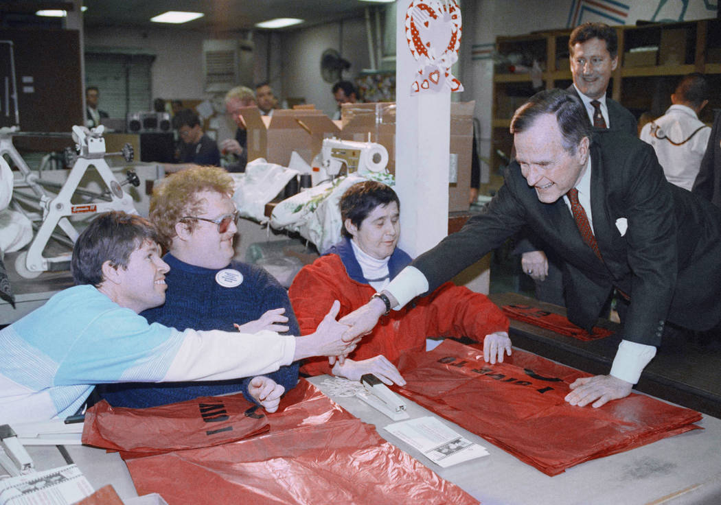 Pres. George H. W. Bush, right, stretches to shake hands with an unidentified patient at Opportunity Village, Thursday, Feb. 6, 1992, Las Vegas, Nev. President Bush visited the center for people w ...