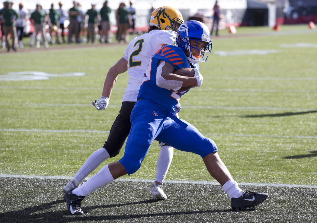 Bishop Gorman running back Amod Cianelli (23) spins into the end zone for a touchdown past Bishop Manogue wide receiver Colby Crisp (2) during the first half of the NIAA high school football champ ...