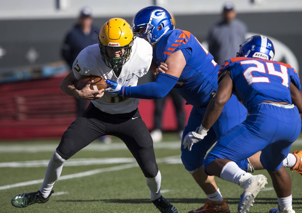 Bishop Manogue quarterback Drew Scolari (12) gets sacked by Bishop Gorman center Daniel Cooke (54) and free safety Cyrus Moss (24) during the first half of the NIAA high school football championsh ...