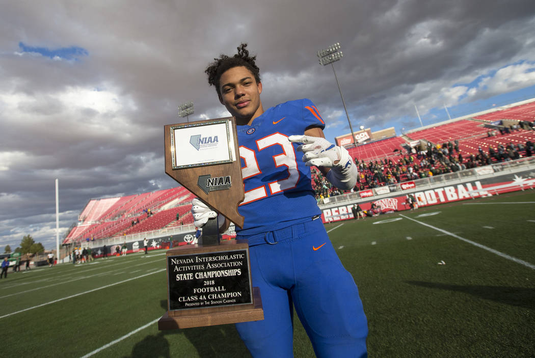 Bishop Gorman running back Amod Cianelli (23) celebrates with the trophy after Gorman defeated Reno's Bishop Manogue 69-26 in the NIAA high school football championship at Sam Boyd Stadium in Las ...
