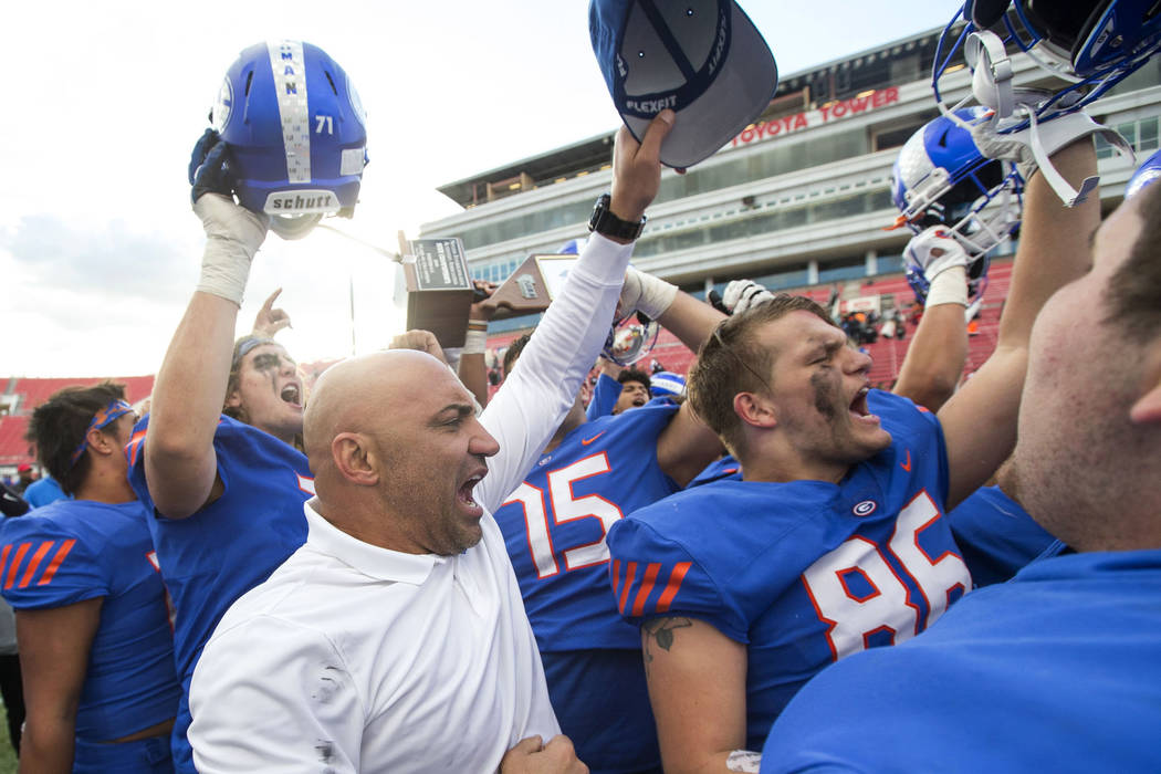Bishop Gorman coach Kenny Sanchez and his players celebrate after defeating Reno's Bishop Manogue 69-26 in the NIAA high school football championship at Sam Boyd Stadium in Las Vegas on Saturday, ...
