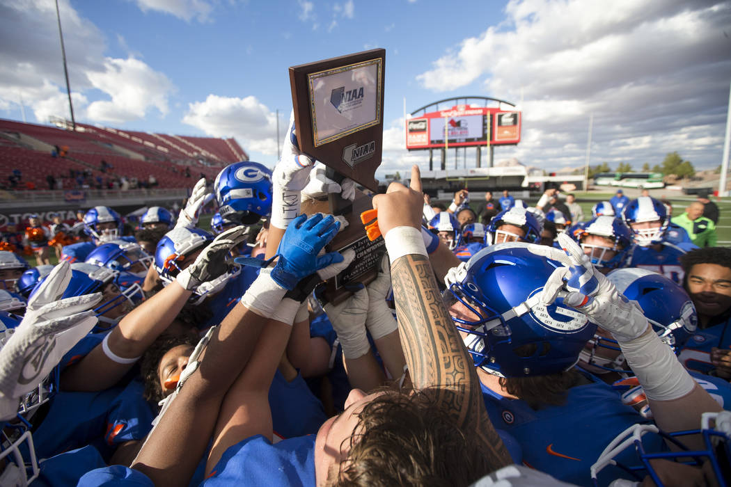 Bishop Gorman players celebrate with the trophy after defeating Reno's Bishop Manogue 69-26 in the NIAA high school football championship at Sam Boyd Stadium in Las Vegas on Saturday, Dec. 1, 2018 ...