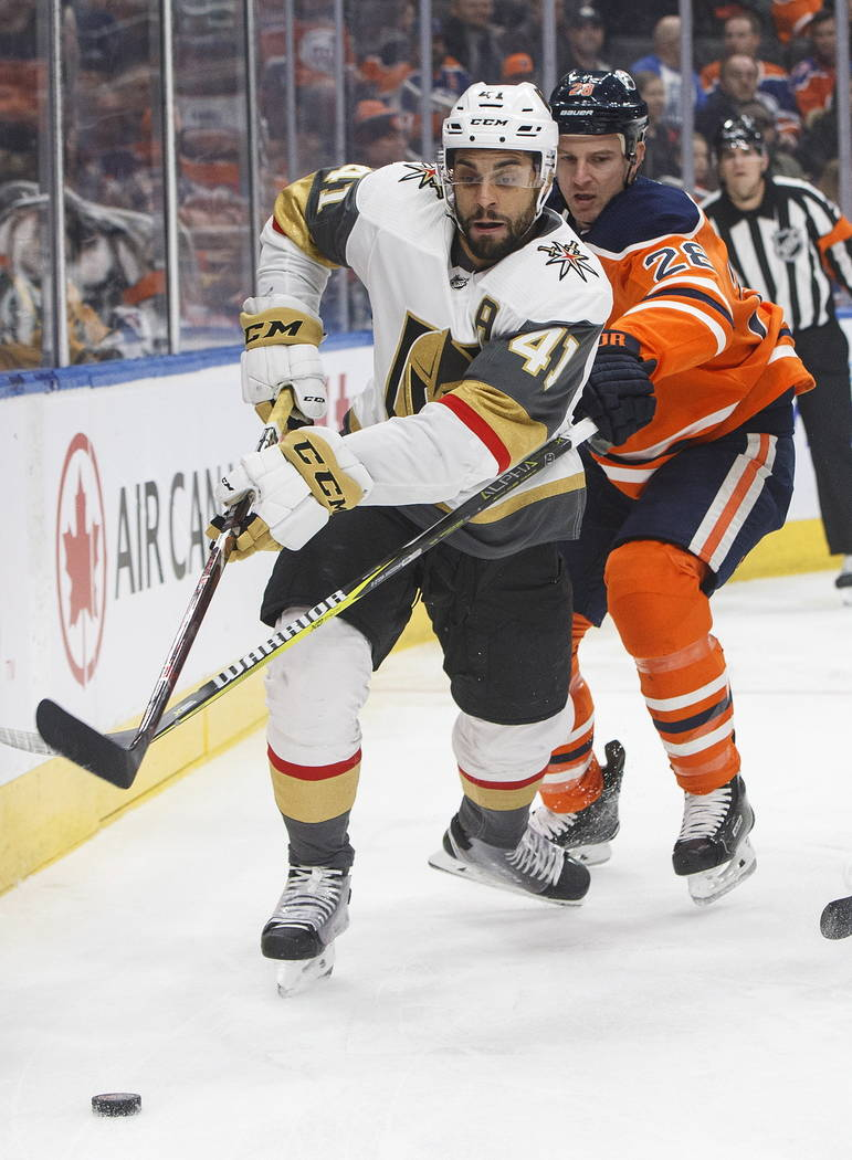 Vegas Golden Knights' Pierre-Edouard Bellemare (41) and Edmonton Oilers' Kyle Brodziak (28) battle for the puck during the first period of an NHL hockey game Saturday, Dec. 10, 2018, in Edmonton, ...
