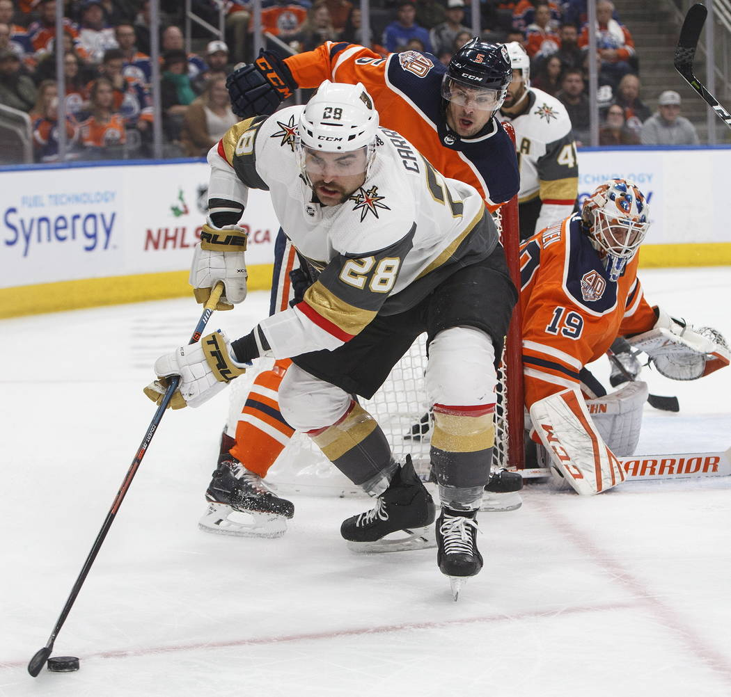 Vegas Golden Knights' William Carrier (28) is chased by Edmonton Oilers' Kevin Gravel (5) during the first period of an NHL hockey game Saturday, Dec. 1, 2018, in Edmonton, Alberta. (Jason Franson ...