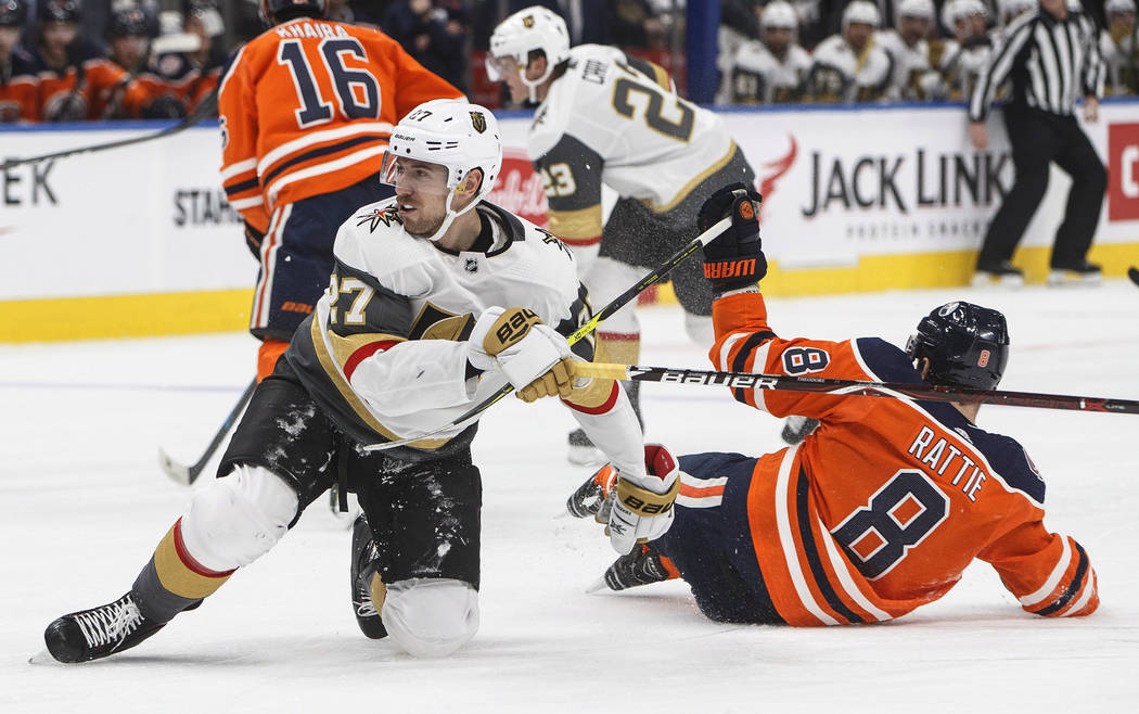 Vegas Golden Knights' Shea Theodore (27) and Edmonton Oilers' Ty Rattie (8) collide during the third period of an NHL hockey game Saturday, Dec. 1, 2018, in Edmonton, Alberta. (Jason Franson/The C ...