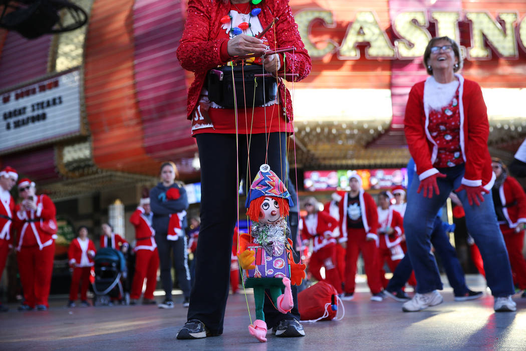 A woman makes a marionette dance during a Zumba warm up dance before the 14th annual Las Vegas Great Santa Run at the Fremont Street Experience 3rd Street Stage in Las Vegas, Saturday, Dec. 1, 201 ...