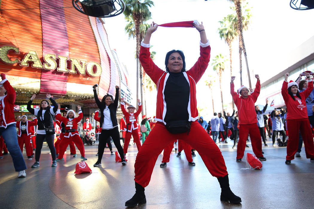 Miriam Chavez of Las Vegas dances to Zumba before the 14th annual Las Vegas Great Santa Run at the Fremont Street Experience 3rd Street Stage in Las Vegas, Saturday, Dec. 1, 2018. The event benefi ...