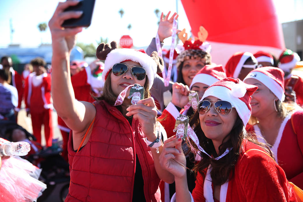 Maia Neri, left, and Judith Caro of Las Vegas, take a photo at finish line of the 14th annual Las Vegas Great Santa Run in downtown Las Vegas, Saturday, Dec. 1, 2018. The event benefits Opportunit ...