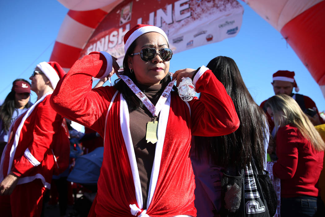 Maricel Manuel of Las Vegas wears her medal at the finish line of the 14th annual Las Vegas Great Santa Run in downtown Las Vegas, Saturday, Dec. 1, 2018. The event benefits Opportunity Village. E ...
