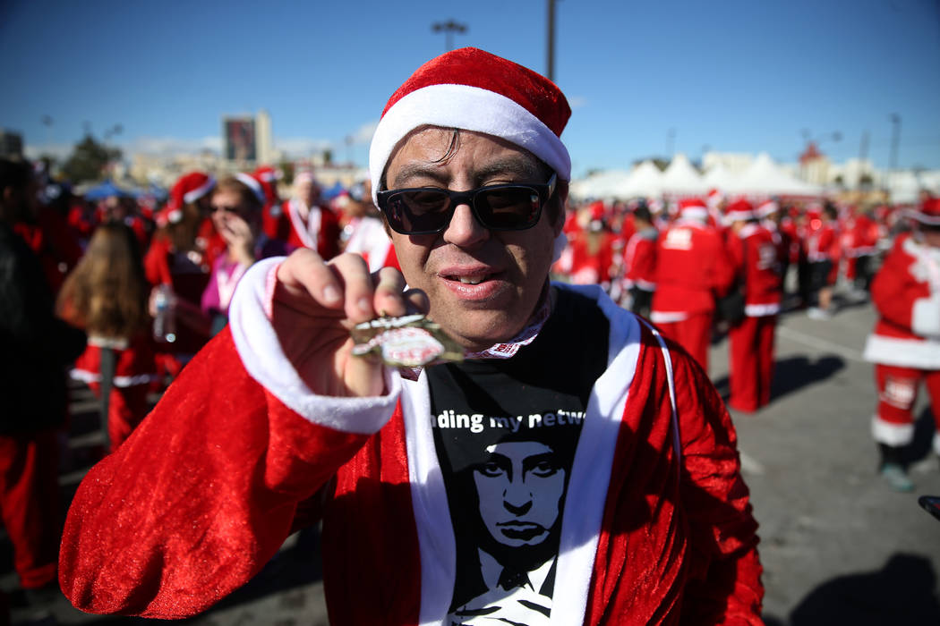 Brandon Bredsguard, 32, employee with Opportunity Village, shows his medal at the finish line of the 14th annual Las Vegas Great Santa Run in downtown Las Vegas, Saturday, Dec. 1, 2018. The event ...