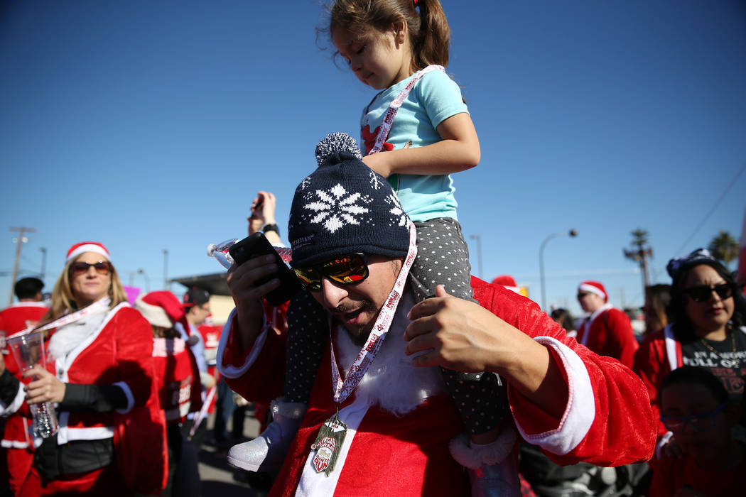 Derek Torres of Las Vegas with his daughter Zara, 3, wear their medals at the finish line of the 14th annual Las Vegas Great Santa Run in downtown Las Vegas, Saturday, Dec. 1, 2018. The event bene ...