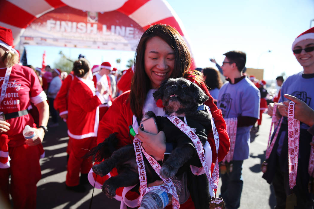 Madison Lai of Las Vegas with her dog Juju receive their medals at the finish line of the 14th annual Las Vegas Great Santa Run in downtown Las Vegas, Saturday, Dec. 1, 2018. The event benefits Op ...