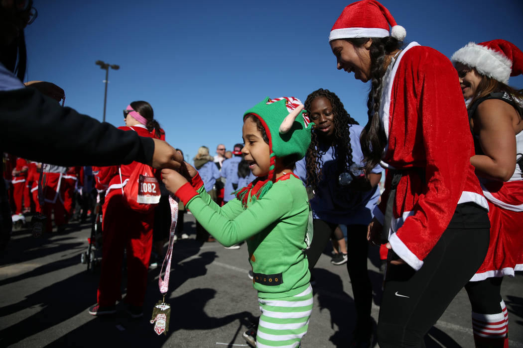 Monica Arriaga of Las Vegas with her son Autlan, 7, receive their medals at the finish line of the 14th annual Las Vegas Great Santa Run in downtown Las Vegas, Saturday, Dec. 1, 2018. The event be ...
