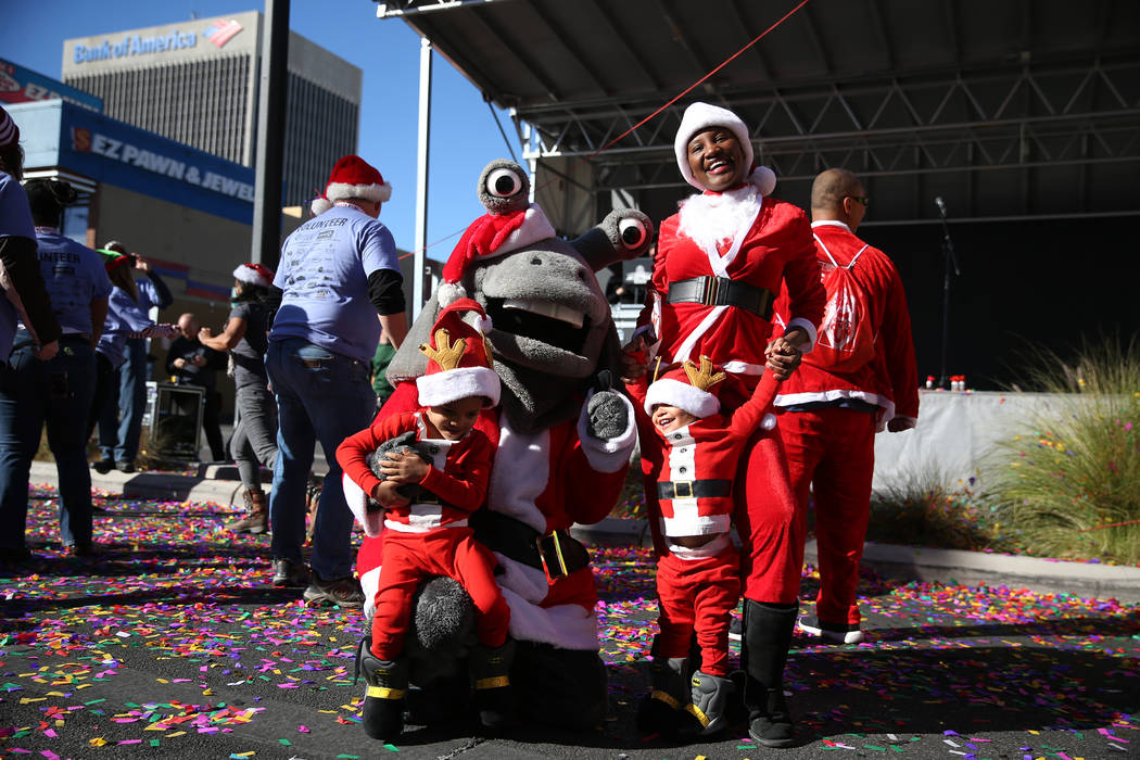 Susan Kikuli, top right, with her two children David Nelson, 4, left, and Chris Nelson, 2, take a photo with Las Vegas 51's mascot Cosmo during the 14th annual Las Vegas Great Santa Run in downtow ...