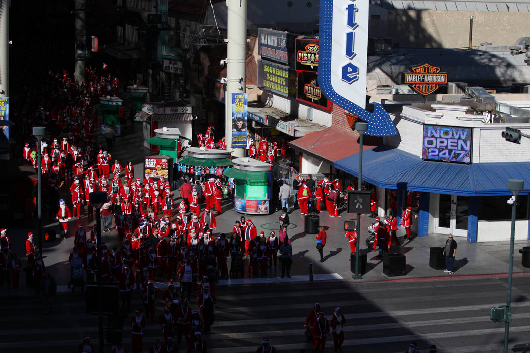People at the Fremont Street Experience make their way to the start line for the 14th annual Las Vegas Great Santa Run in Las Vegas, Saturday, Dec. 1, 2018. The event benefits Opportunity Village. ...