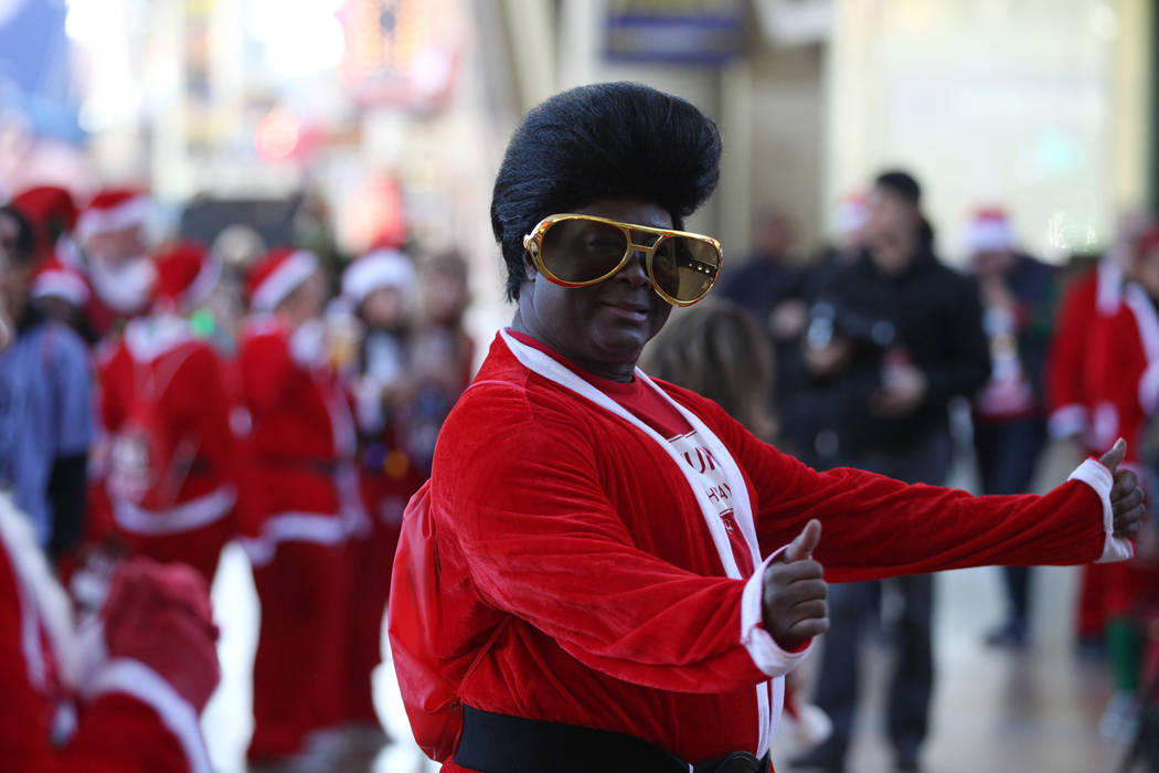 Larry Edwards of Las Vegas dance before the 14th annual Las Vegas Great Santa Run at the Fremont Street Experience 3rd Street Stage in Las Vegas, Saturday, Dec. 1, 2018. The event benefits Opportu ...
