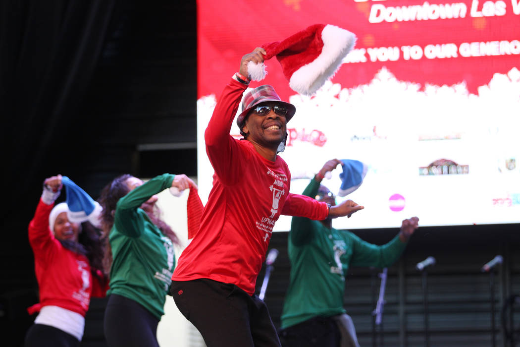 Jerry Johnson with Strong In 1 Fitness leads a Zumba dance in front of a crowd of people before the 14th annual Las Vegas Great Santa Run at the Fremont Street Experience 3rd Street Stage in Las V ...
