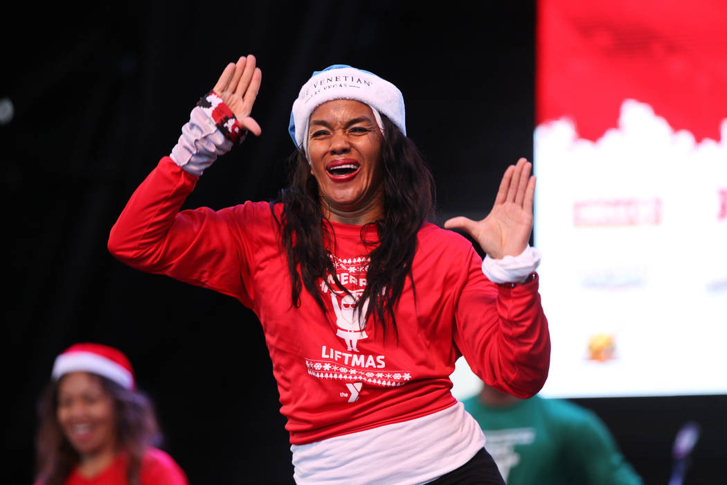 Kristi Mydell with Strong In 1 Fitness leads a Zumba dance in front of a crowd of people before the 14th annual Las Vegas Great Santa Run at the Fremont Street Experience 3rd Street Stage in Las V ...