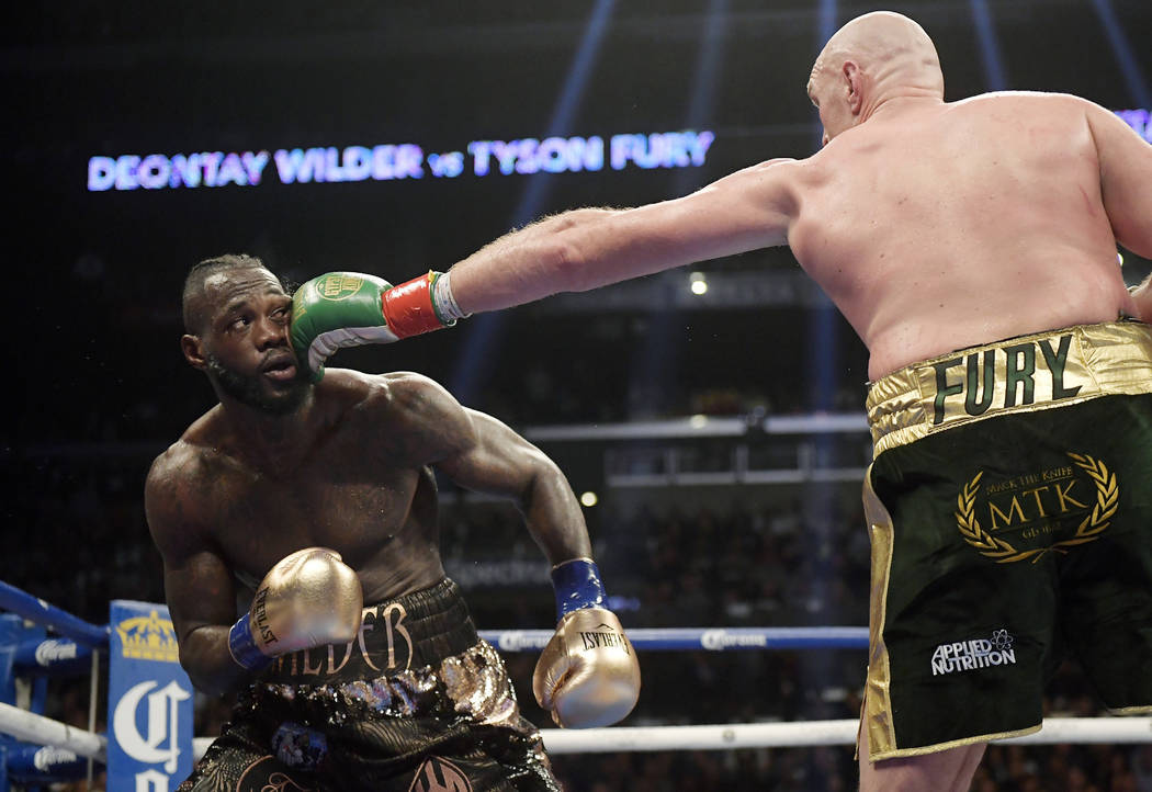 Tyson Fury, right, of England, connects with Deontay Wilder during a WBC heavyweight championship boxing match, Saturday, Dec. 1, 2018, in Los Angeles. (AP Photo/Mark J. Terrill)