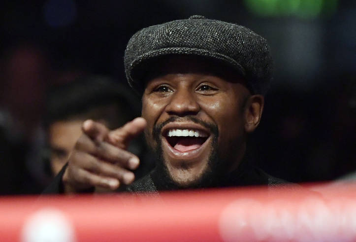 Boxer Floyd Mayweather points to someone in the crowd as he watches a boxing match between Deontay Wilder and Tyson Fury, of England, for the WBC heavyweight championship, Saturday, Dec. 1, 2018, ...