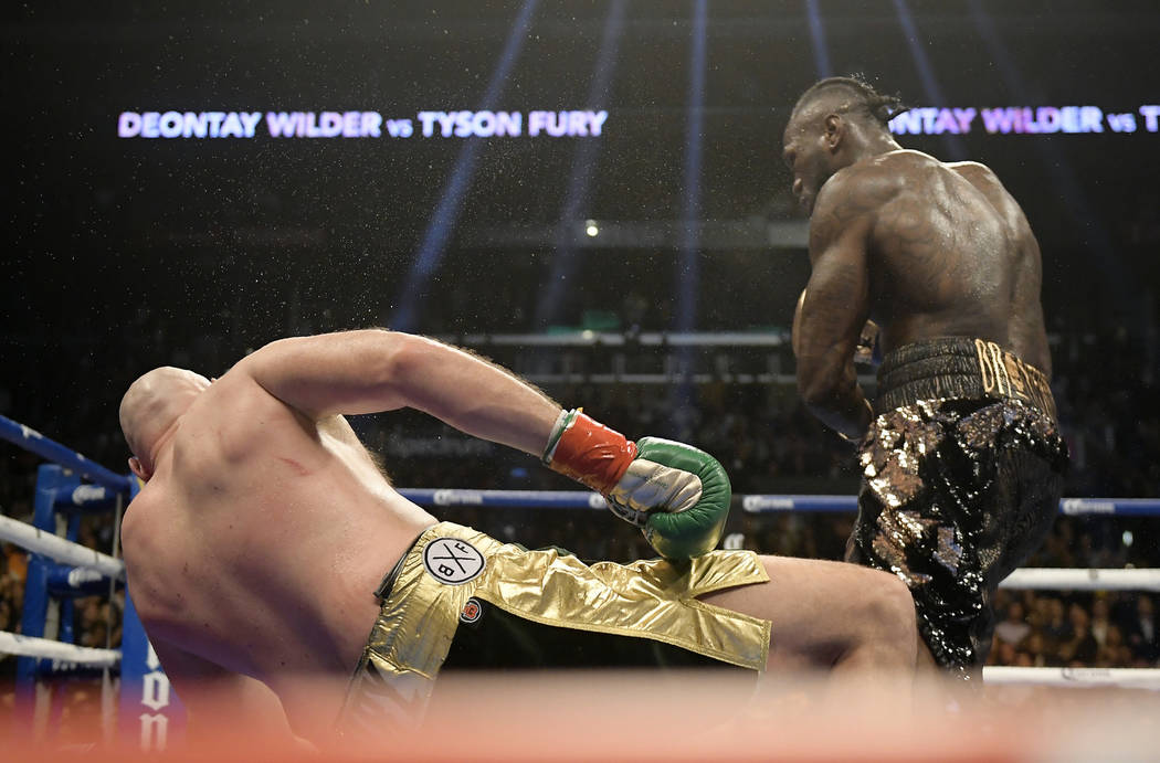 Deontay Wilder, right, knocks down Tyson Fury, of England, during the 12th round of a WBC heavyweight championship boxing match, Saturday, Dec. 1, 2018, in Los Angeles. (AP Photo/Mark J. Terrill)