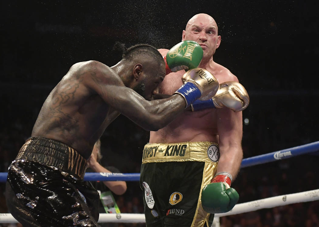 Deontay Wilder, left, connects with Tyson Fury, of England, during a WBC heavyweight championship boxing match Saturday, Dec. 1, 2018, in Los Angeles. (AP Photo/Mark J. Terrill)
