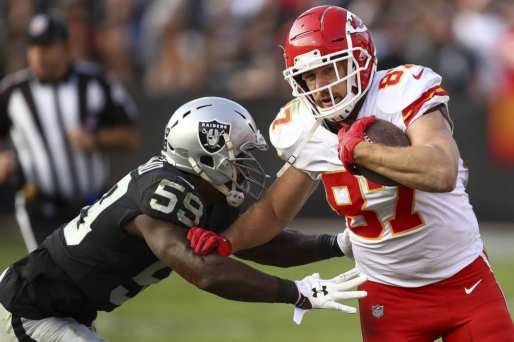 Kansas City Chiefs tight end Travis Kelce (87) runs against Oakland Raiders linebacker Tahir Whitehead (59) during the second half of an NFL football game in Oakland, Calif., Sunday, Dec. 2, 2018. ...